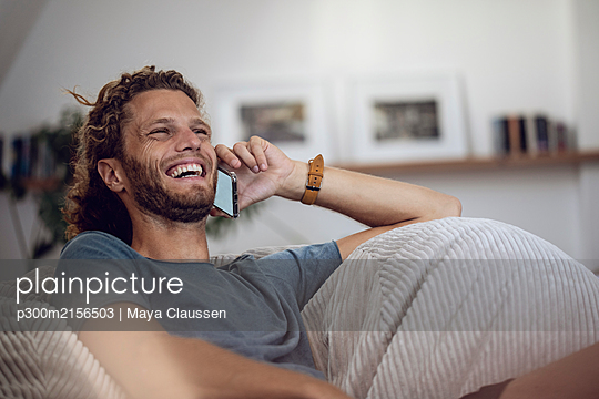 Laughing young man relaxing in beanbag at home talking on the phone - p300m2156503 by Maya Claussen