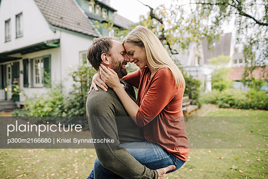 Happy couple kissing in garden, in front of their dream house - p300m2166680 von Kniel Synnatzschke