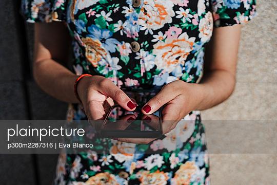 beautiful hispanic woman in city holding mobile phone, Madrid, Spain - p300m2287316 von Eva Blanco