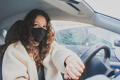 young woman driving with protective mask - p1166m2255161 by Cavan Images