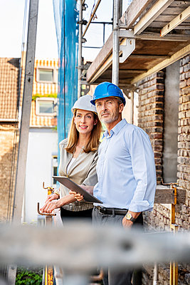 Male professional with digital tablet standing by colleague at construction site - p300m2257124 by Peter Scholl