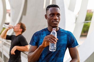 Male athlete looking away while holding water bottle - p300m2277102 by Ignacio Ferrándiz Roig