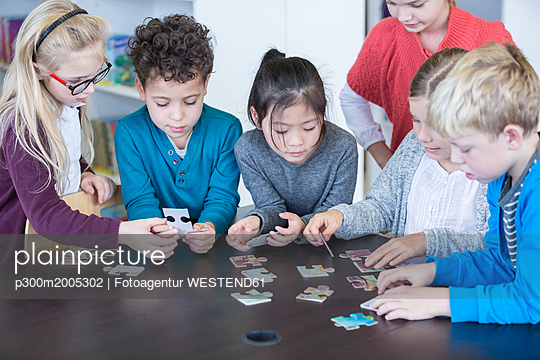 Pupils playing jigsaw puzzle in school together - p300m2005302 von Fotoagentur WESTEND61