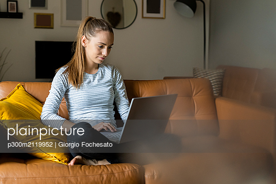 Young woman using laptop on couch at home - p300m2119952 by Giorgio Fochesato
