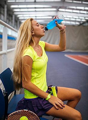 Young tennis player in an indoor tennis center having a rest drinking beverage - p300m1059014f by Marco Govel