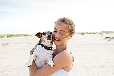 Junge Frau mit Hund am Strand  - p341m1480689 von Mikesch