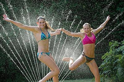 Teenage girls playing in sprinkler - p924m768516f by Pete Saloutos