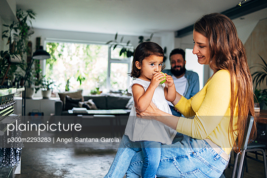 Smiling mother looking at daughter eating fruit while sitting on lap - p300m2293283 by Angel Santana Garcia