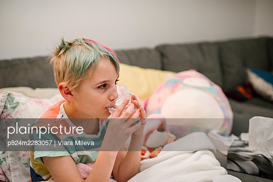 Canada, Ontario, Boy with colorful hair drinking water on sofa - p924m2283057 by Viara Mileva