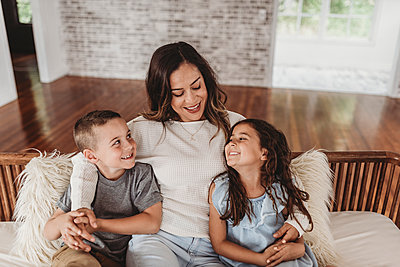 Mother and children smiling at each other while sitting on couch - p1166m2130776 by Cavan Images