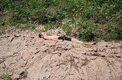 Boy laying in sand - p1169m2016023 by Tytia Habing
