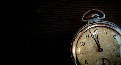 Antique pocketwatch on wooden table - p1427m2169127 by Tetra Images