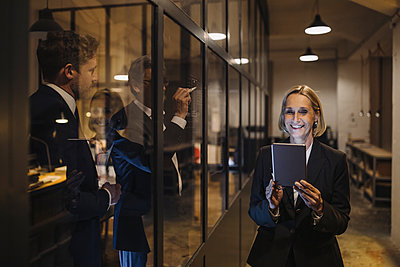 Smiling businesswoman using tablet and two businessmen working on drawing on glass pane in office - p300m2154906 by Gustafsson