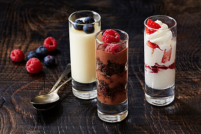 Still life with three desserts in glasses with raspberry and blackberry garnish - p429m2068711 by Danielle Wood