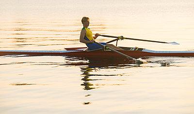 Caucasian man rowing on lake - p555m1303400 by Pete Saloutos