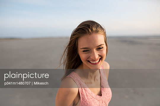 Young woman on St. Peter-Ording beach - p341m1480707 by Mikesch