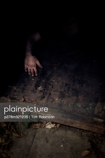 Hand lying on floor - p378m921235 by Tim Robinson