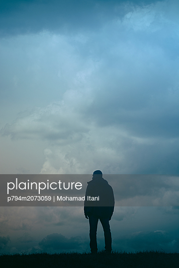 Man standing in field on a gloomy day  - p794m2073059 by Mohamad Itani