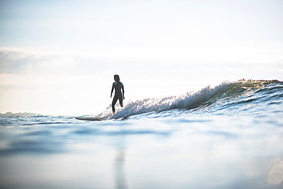 Asian Woman surfing waves during sunrise summer surf session - p1166m2279621 by Cavan Images