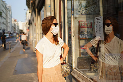 A woman looks at a window shop - p1610m2208786 by myriam tirler