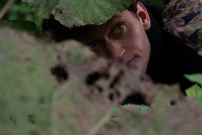 Junger Mann schaut unter Blättern hervor - p1650m2231571 von Hanna Sachau