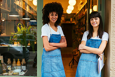 Portrait of two smiling women standing in entrance door of a store - p300m1567912 by Bonninstudio
