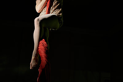 Waist down view of young female aerial acrobat wrapped around  silk rope - p429m1224257 by GS Visuals