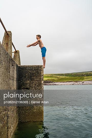 Boy on pier prepares for a backflip into the sea - p1082m2196365 by Daniel Allan