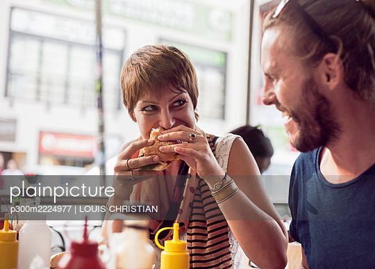 Young woman eating burger while sitting in cafe with mid adult man - p300m2224977 by LOUIS CHRISTIAN