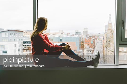 Frau blickt nachdenklich aus dem Fenster - p432m2090022 von mia takahara