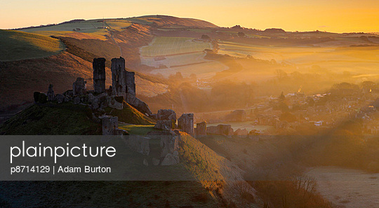 Misty winters sunrise over the village and castle at Corfe - p8714129 by Adam Burton
