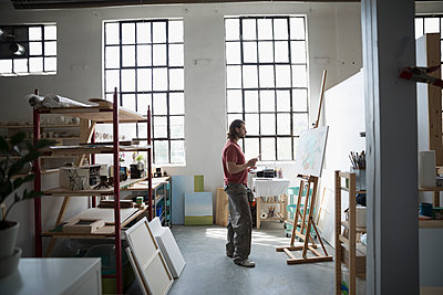 Male painter painting at canvas on easel in art studio - p1192m1490156 by Hero Images