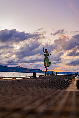 Woman on wooden pier at sunrise, New Zealand - p1455m2204892 by Ingmar Wein
