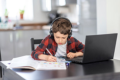 Boy wearing headphones writing on book while studying at home - p300m2282911 by William Perugini
