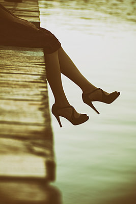 Young woman sat on the wharf by the sea  - p794m1538621 by Mohamad Itani