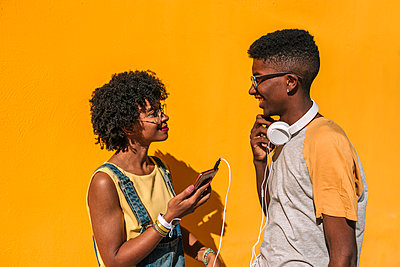 Couple of black teenagers listening to music with a yellow background - p1166m2123536 by Cavan Images