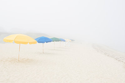 Empty beach with umbrellas and fog - p1427m2254874 by Chris Hackett