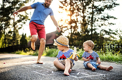 Mature man playing hopscotch while his little children watching him - p300m2060121 by HalfPoint