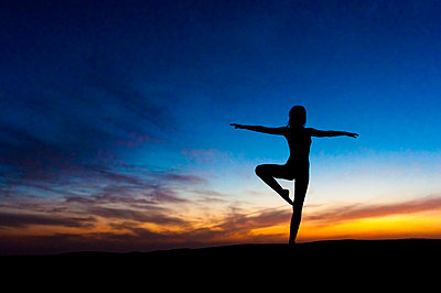 Silhouette of woman dancing at sunset, Gran Canaria, Spain - p300m2197913 by Daniel Ingold