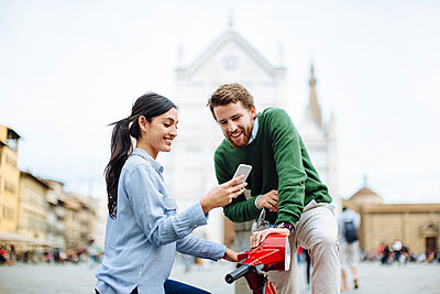 Woman showing smart phone to boyfriend while sitting on Vespa in Florence, Italy - p300m2203110 by Sofie Delauw