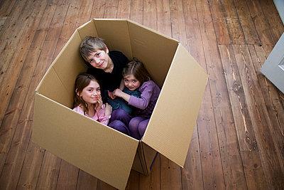 Three children sitting inside a box - p4296555f by Adie Bush