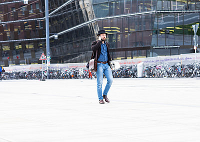 Male skateboarder strolling in city square making smartphone call, Freiburg, Baden-Wurttemberg, Germany - p429m2091581 by Sigrid Gombert