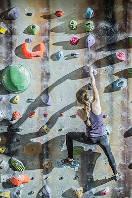 Athlete climbing rock wall in gym - p555m1411963 by John Fedele