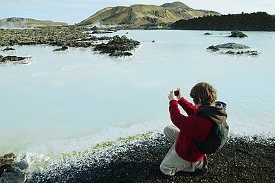 Boy photographing around the Blue Lagoon, Iceland - p623m803818f by Claire Nijnikoff