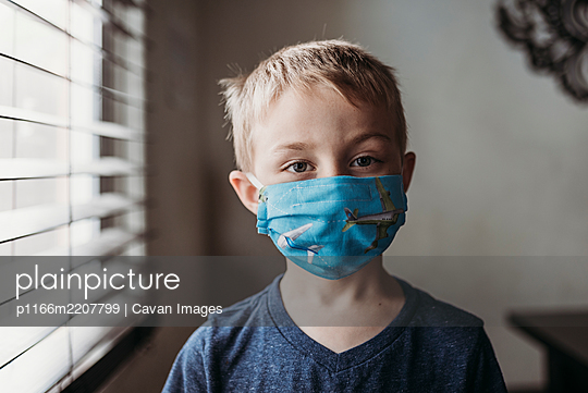 Portrait of young school aged boy with mask on with at home - p1166m2207799 by Cavan Images