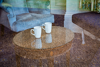 Looking through a window into an old room with chair, glass table and two abndoned white ceramic mugs. - p1057m1463265 by Stephen Shepherd