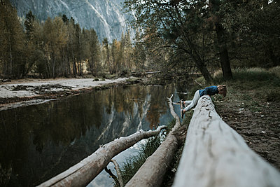 Side view of boy lying on log by lake at Yosemite National Park - p1166m1526866 by Cavan Images