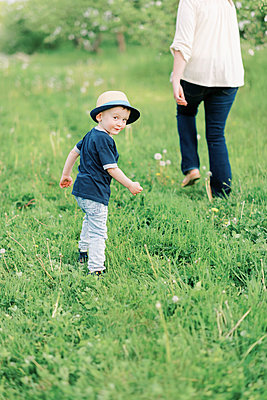 A cute toddler boy looking into the camera while walking with his mom - p1166m2193811 by Cavan Images