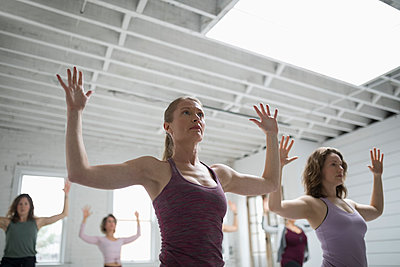 Focused women practicing yoga in yoga class - p1192m1583323 by Hero Images