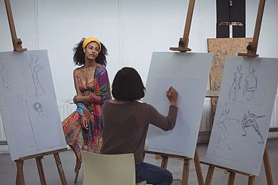 Female artist drawing a sketch of woman on canvas - p1315m1514604 by Wavebreak